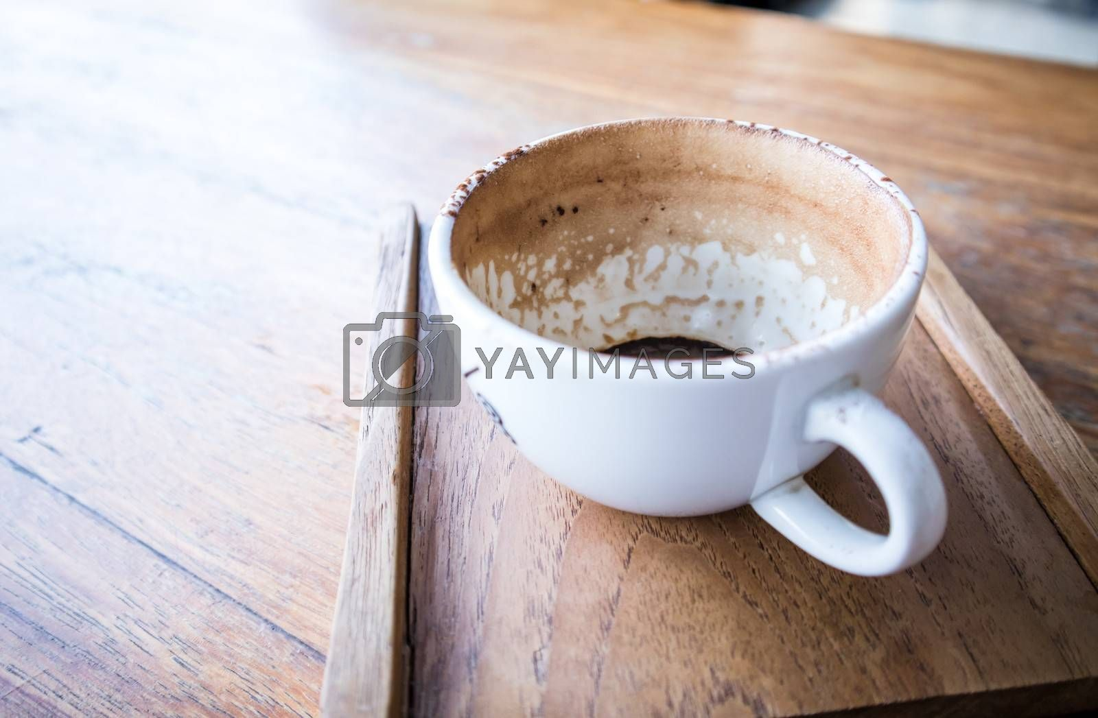 Finished Empty coffee cup on the wooden table with a wooden tray .close up view