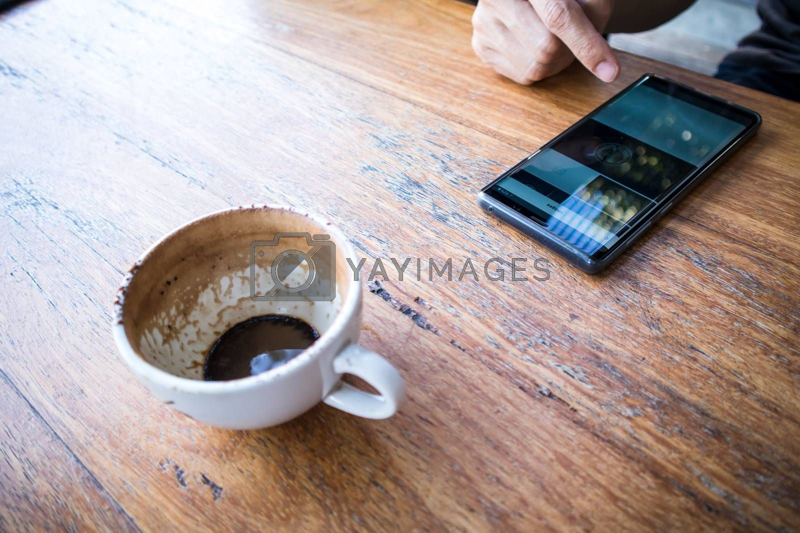 Close up of a right hand using smartphone with a Finished Empty Cup of Coffee on a brown wooden table. view from above