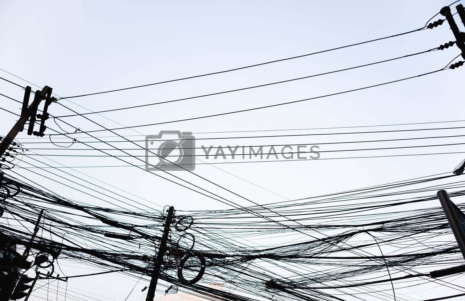 Messy electrical wires looking from street level on clear sky city background