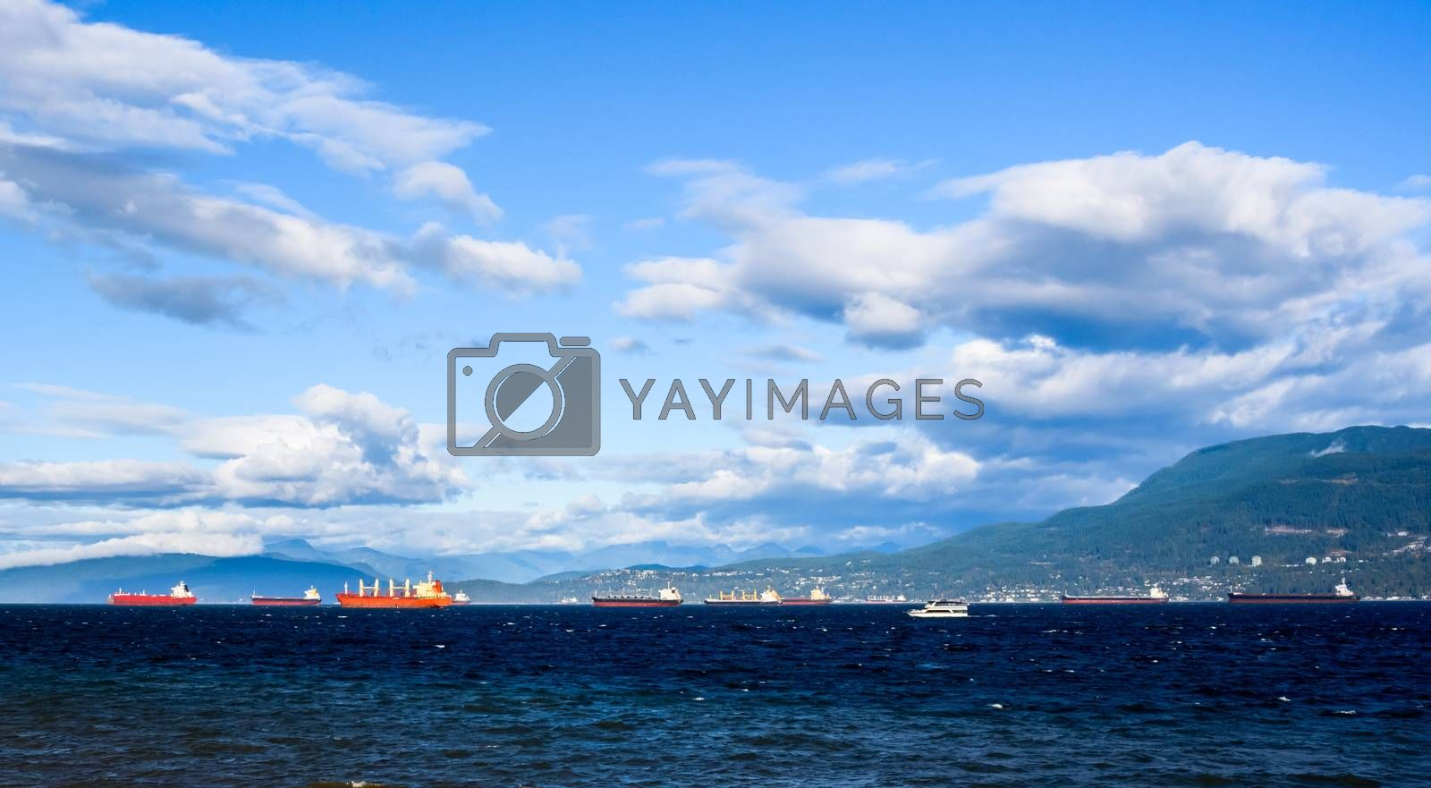 Cargo ships and other boats anchored in bay under a few clouds and blue sky near Vancouver, British Columbia, Canada.