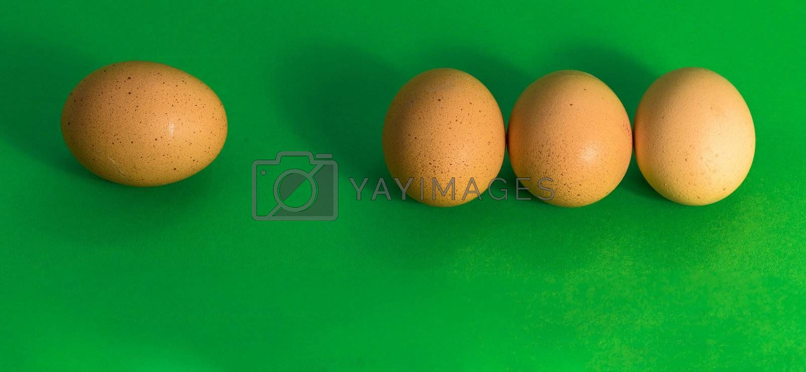 Abstract picture at Easter, three eggs lying close to each other and a single sad egg further away, on grass-green background, concept lonely