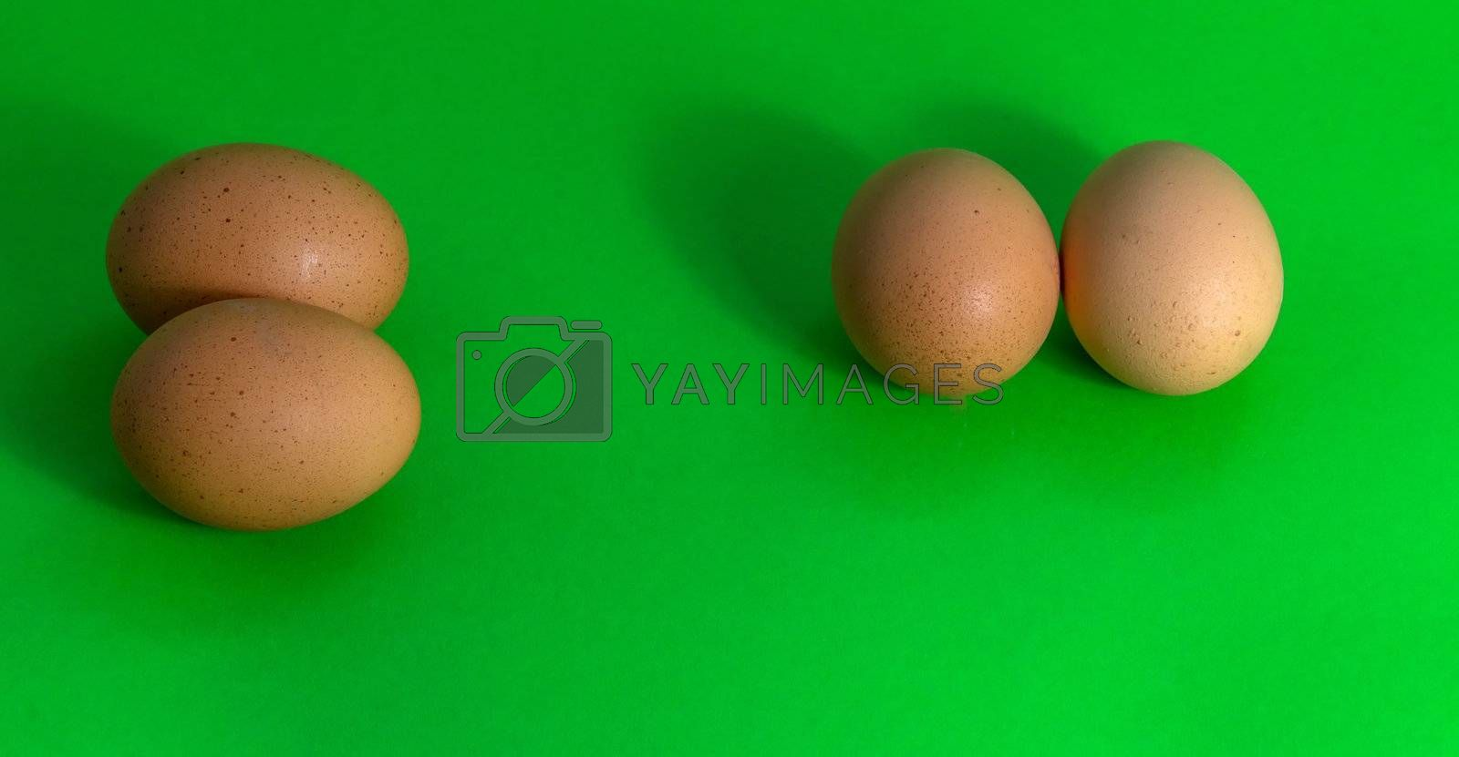 Abstract picture of Easter, two groups with two eggs on a uniformly green background, concept
