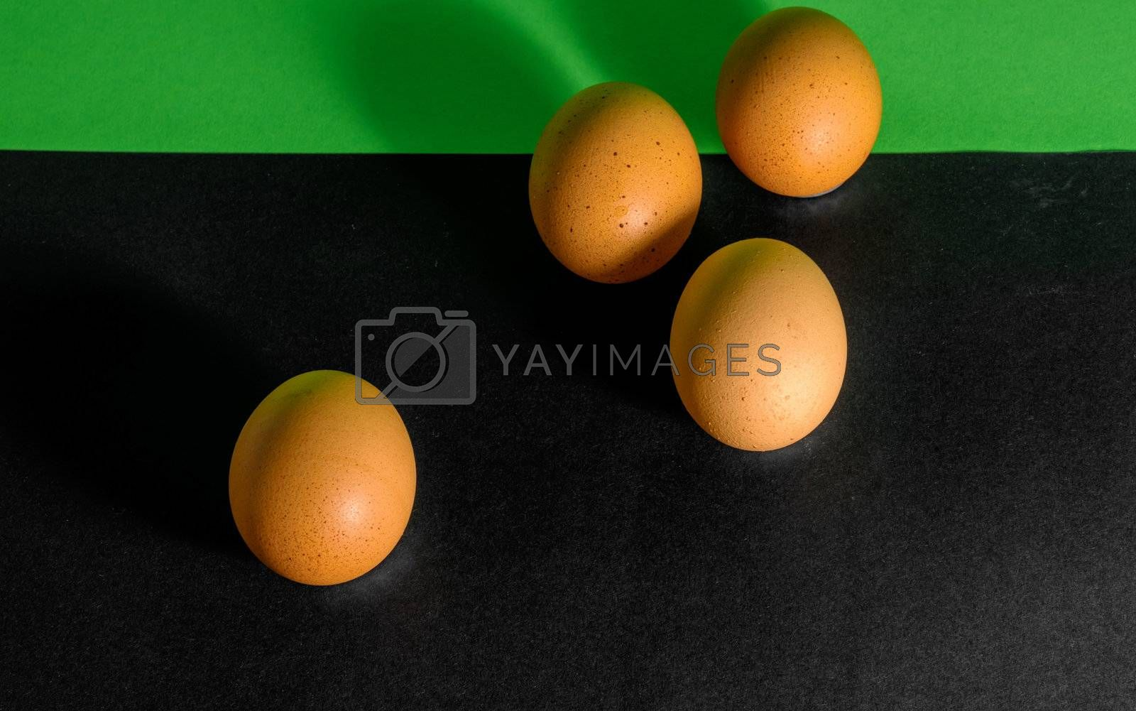 Abstract picture at Easter, four eggs from a predominantly black and in the upper part green background, concept