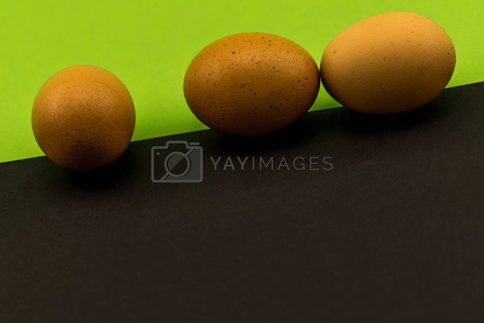 Abstract picture at Easter, three eggs on the oblique borderline of a front black and rear green background, concept