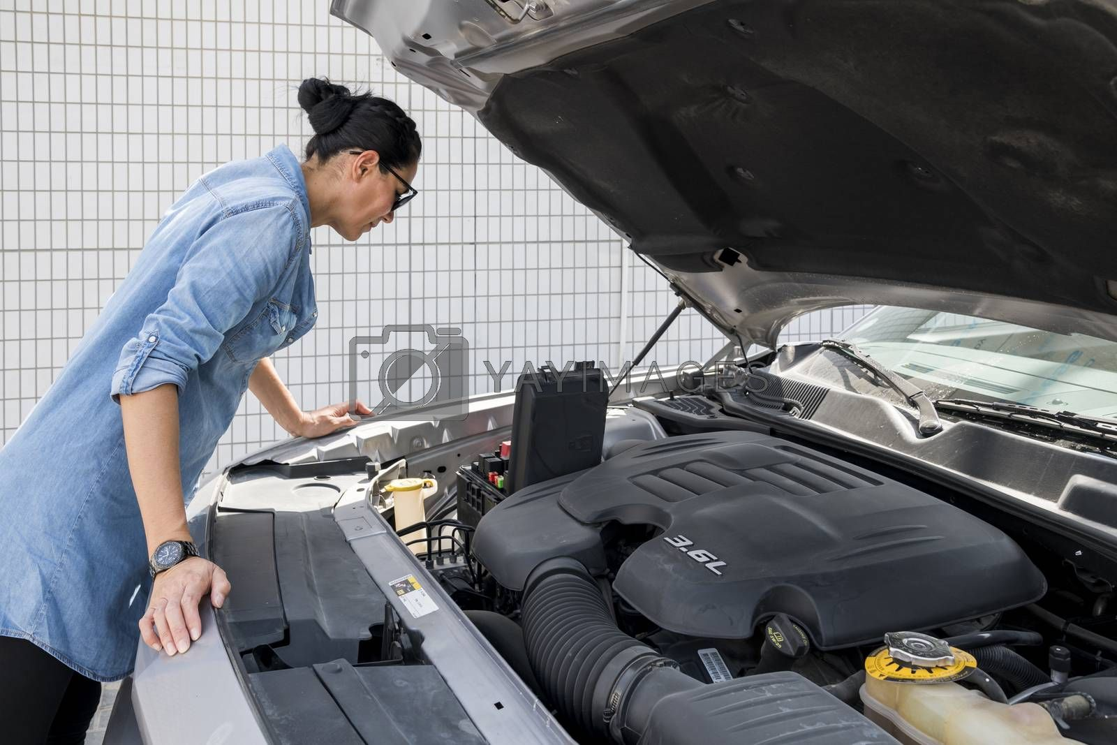 Woman looking at fuse box of her sport car