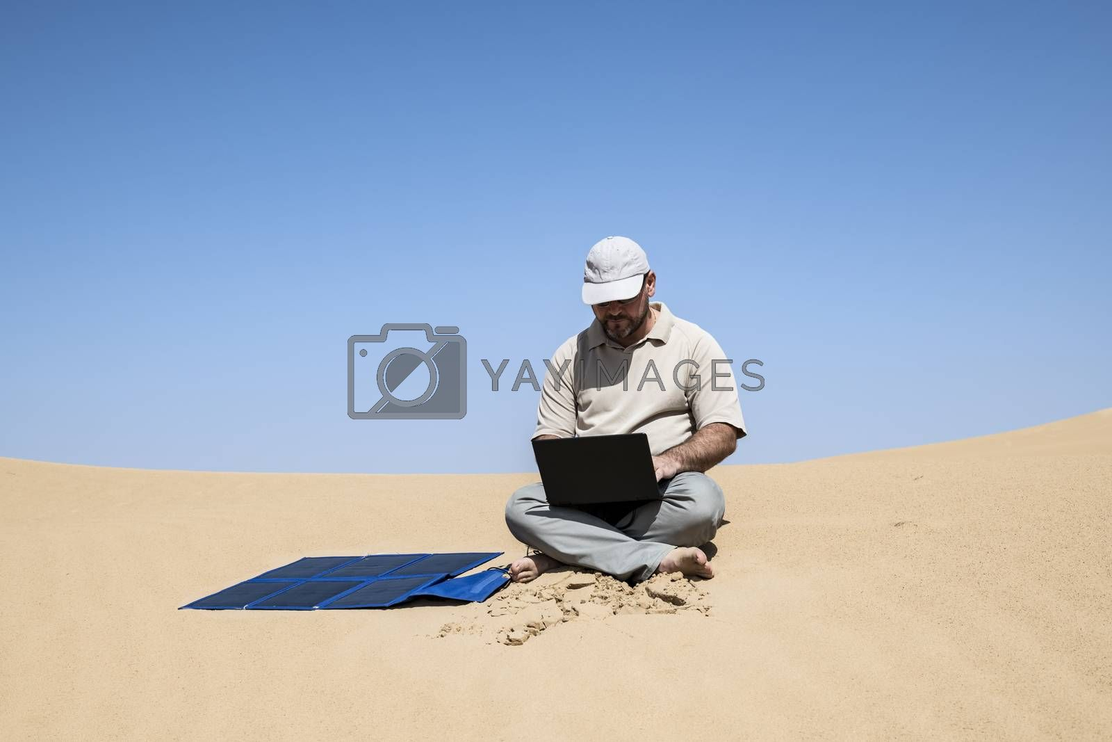 Adult (man) using his computer in the Middle of the dunes by clear sky, using portable flexible solar panels and charger