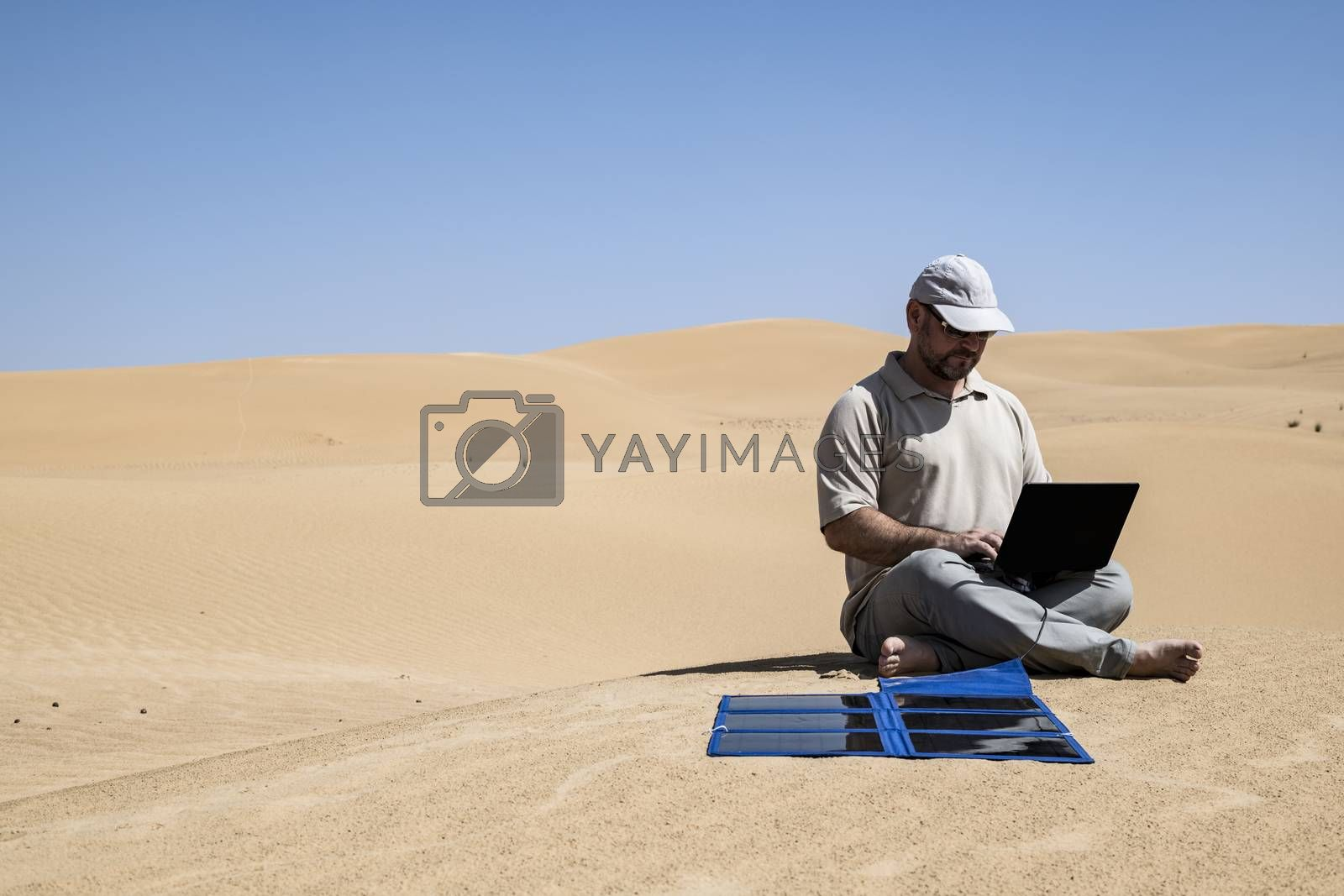 Adult (man) using his laptop in the Middle of the dunes by clear skies and using portable flexible solar panels and charger