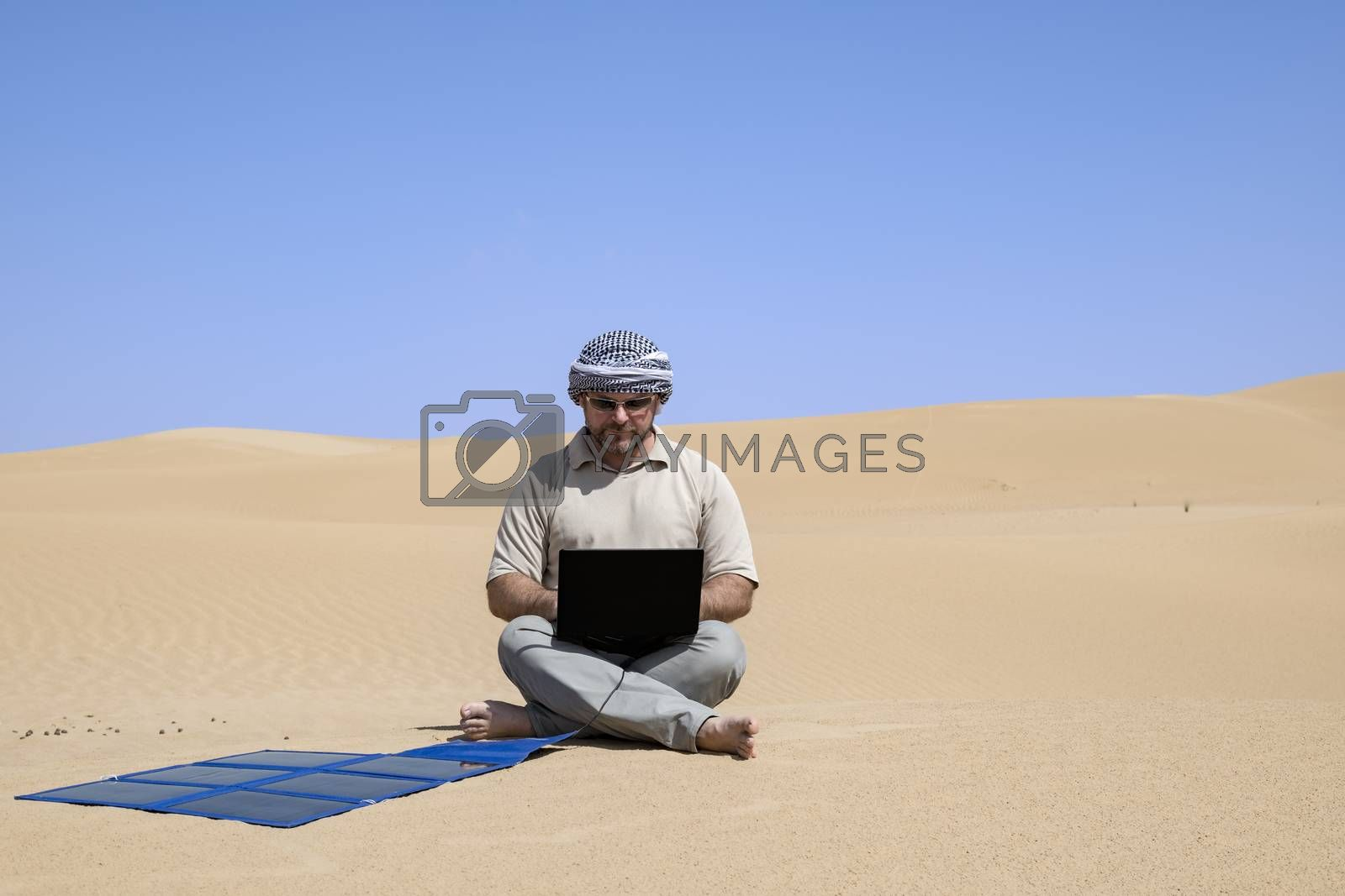 Man (adult) using his computer charging with flexible solar panels in the middle of the dunes.
