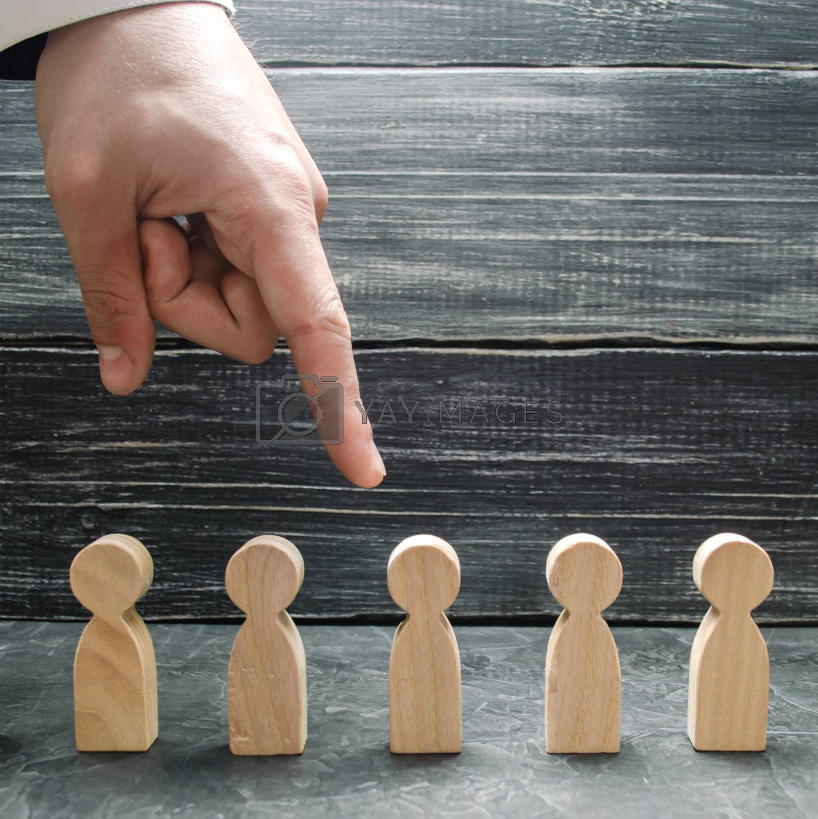 A businessman's hand points to a wooden human figure. Hiring and volnenie employees, pressure, violation of employee rights. The concept of the search for workers, management of human resources.