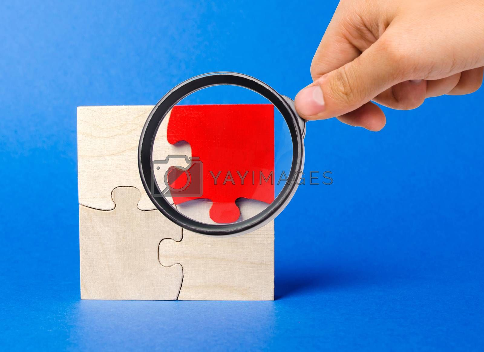A magnifying glass looks at a red wooden puzzles on a blue background. Individual opinion. Stand out from the crowd. Uniqueness. Divergent views. Different concepts to other people.