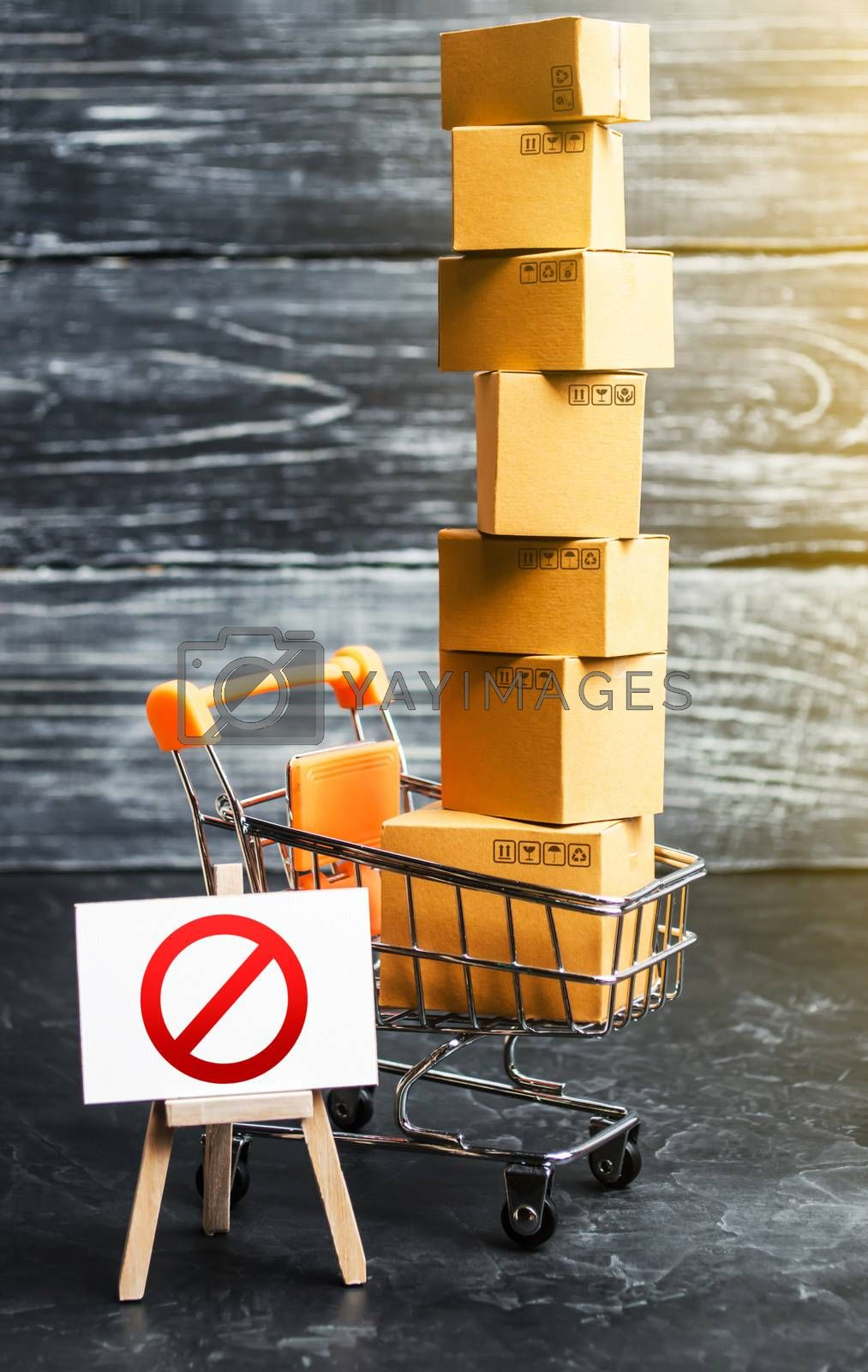 Trading cart with boxes and an easel with a prohibition symbol NO. Internet trade online shopping ban. Restriction on importation goods, proprietary for business. Sanctions and economic restrictions