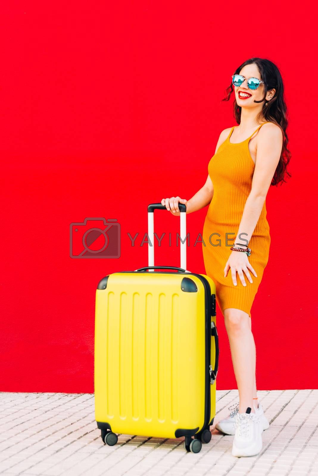 happy woman holding suitcase and smiling while standing.