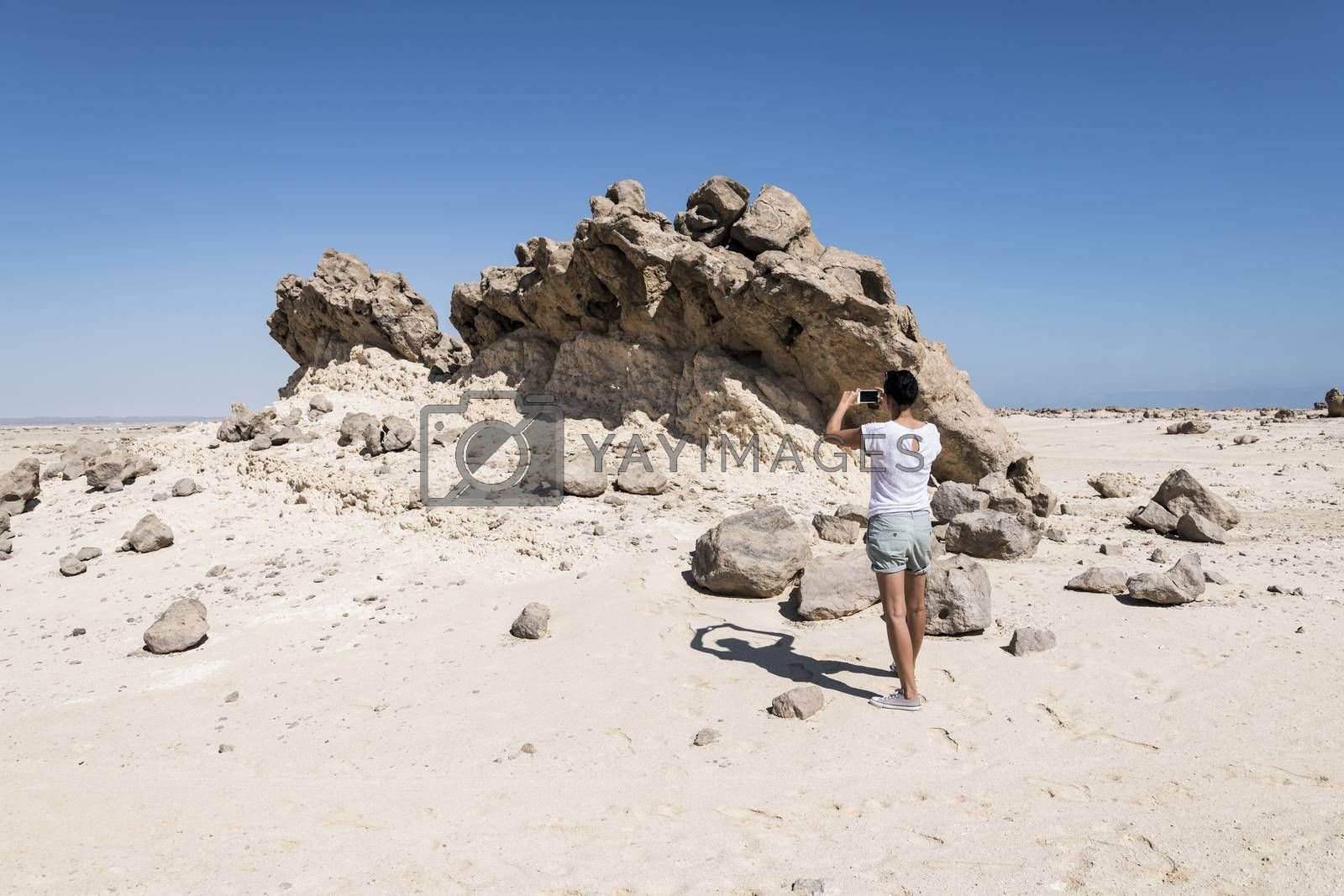 Woman taking stange rocks in picture at Rock Garden (also called Rock Zoo of Duqm or Duqm Stone Park), a famous tourist attraction of a 3 square kilometer of rock formations (shaped by wind, water and other natural forces), limestone and marine fossils, Duqm, Sultanate of Oman