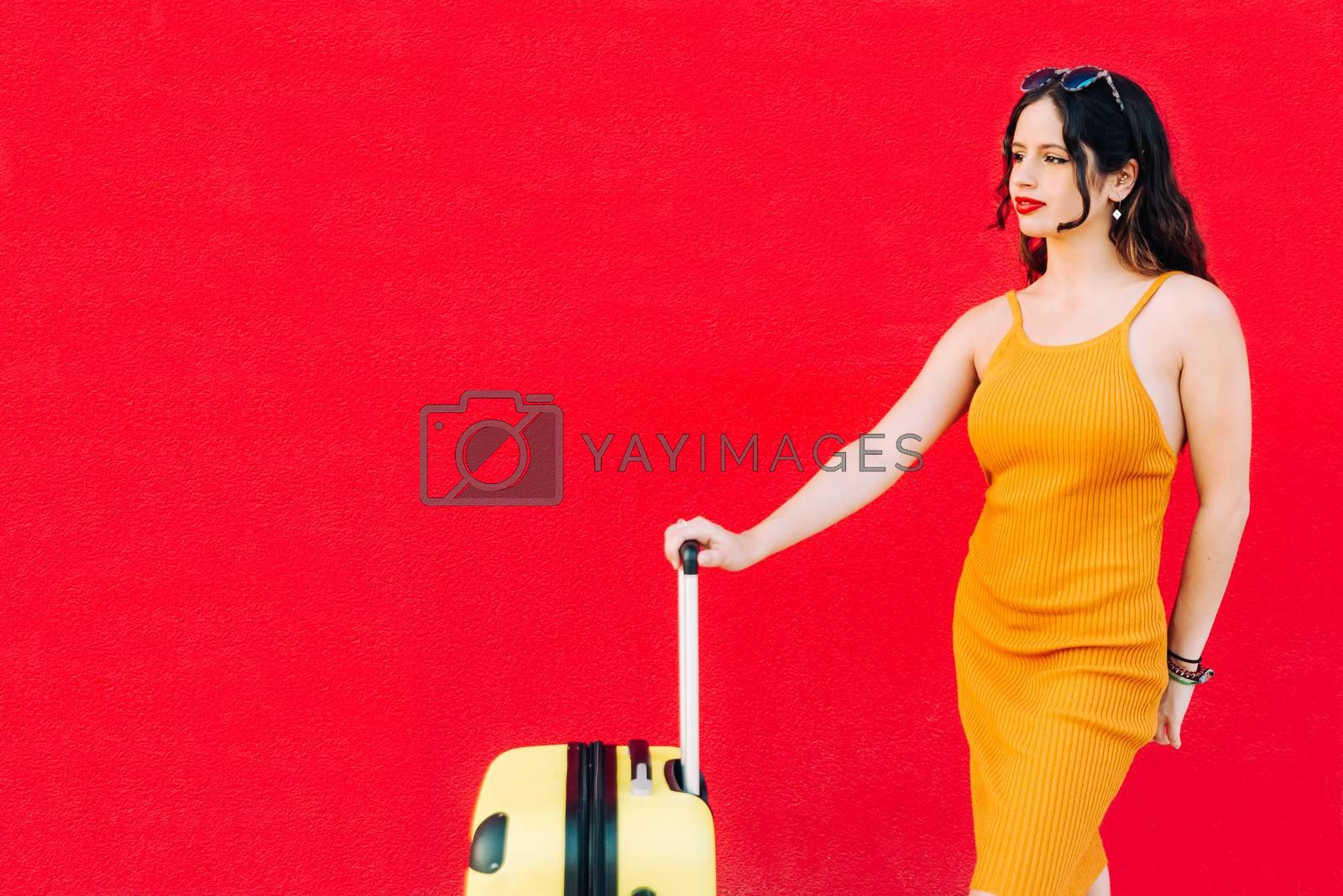 young woman holding suitcase and smiling while standing.