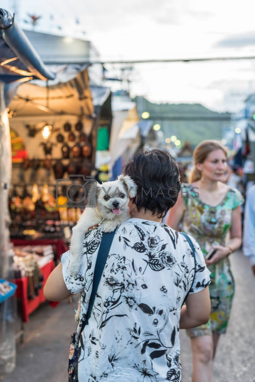 Prachuap Khiri Khan, Thailand - June 17, 2017 : Unidentified woman and the dog walk stroll shopping at Hua Hin night market. The famous night market for travel in Hua Hin is major tourist attraction.