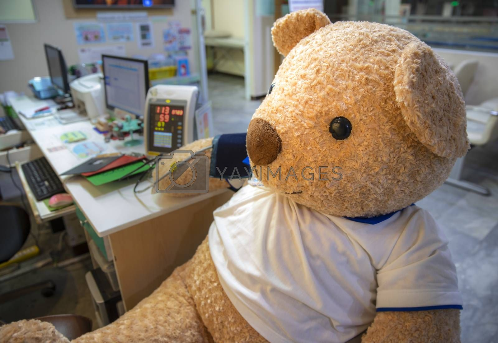 a stuffed toy bear in the clinic screening area by Nawoot