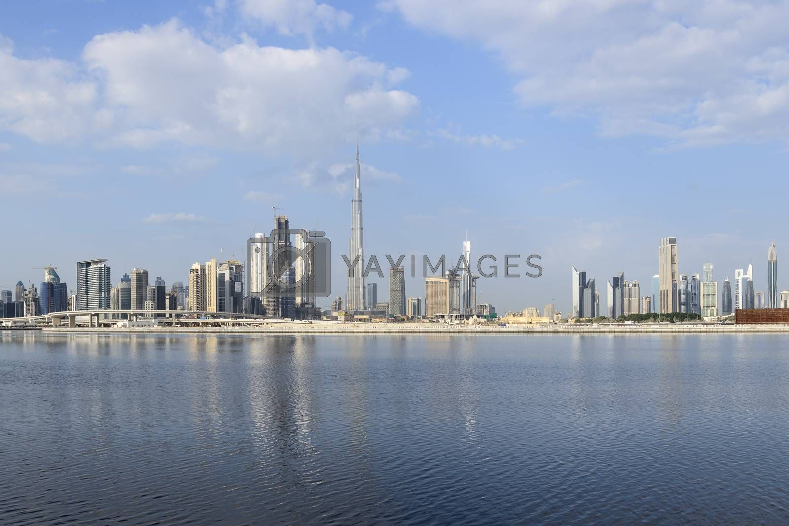 Skyline of Dubai and the iconic Burj Khalifa skyscraper with a partly cloudy sky and winds