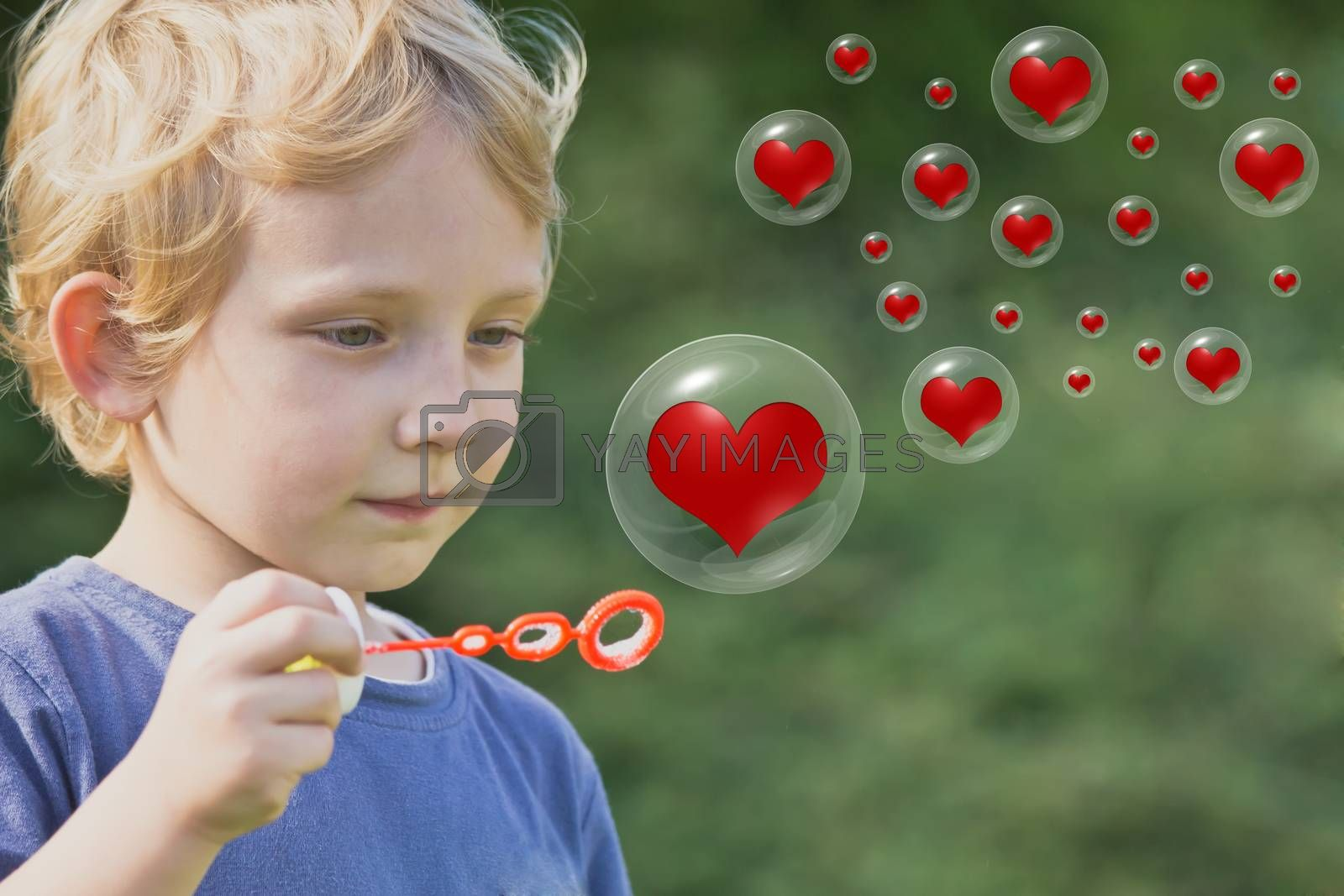 The blond boy is playing with soap bubbles, in which are red hearts
