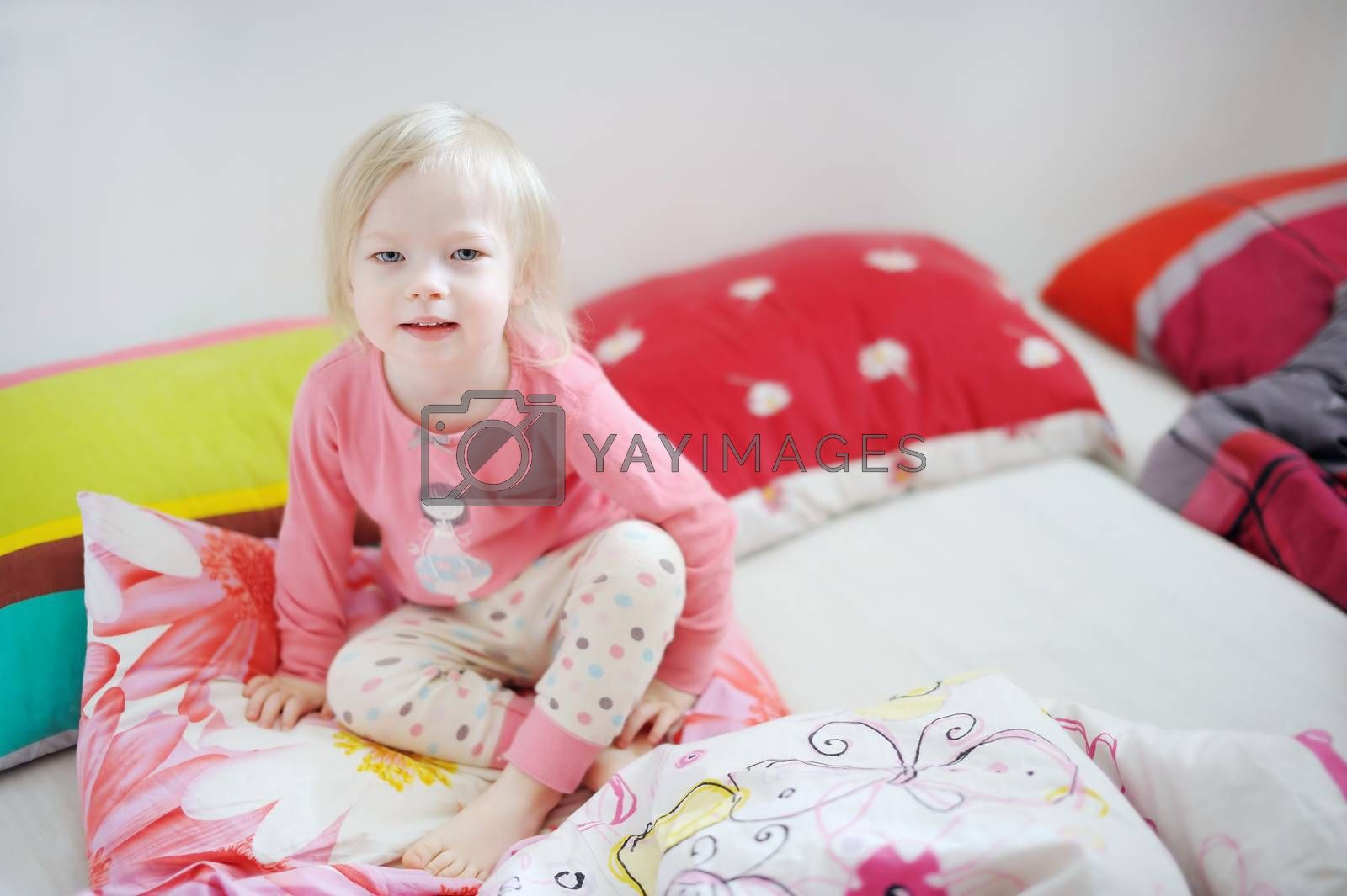 Little toddler girl playing in bed on sunny morning