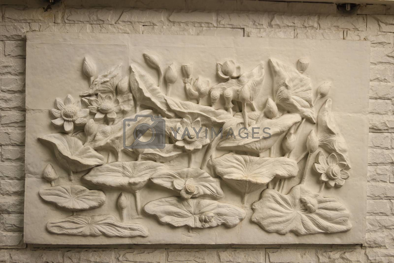 Beautiful white lotus stucco patterned on the boundary wall. Vintage white wall bas-relief stucco in plaster, depicts Lotus flowers background.