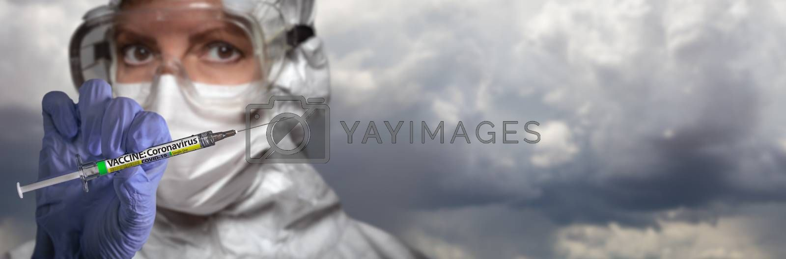 Doctor or Nurse Wearing Surgical Glove Holding Medical Syringe with Coronavirus COVID-19 Vaccine Label Banner of Clouds.