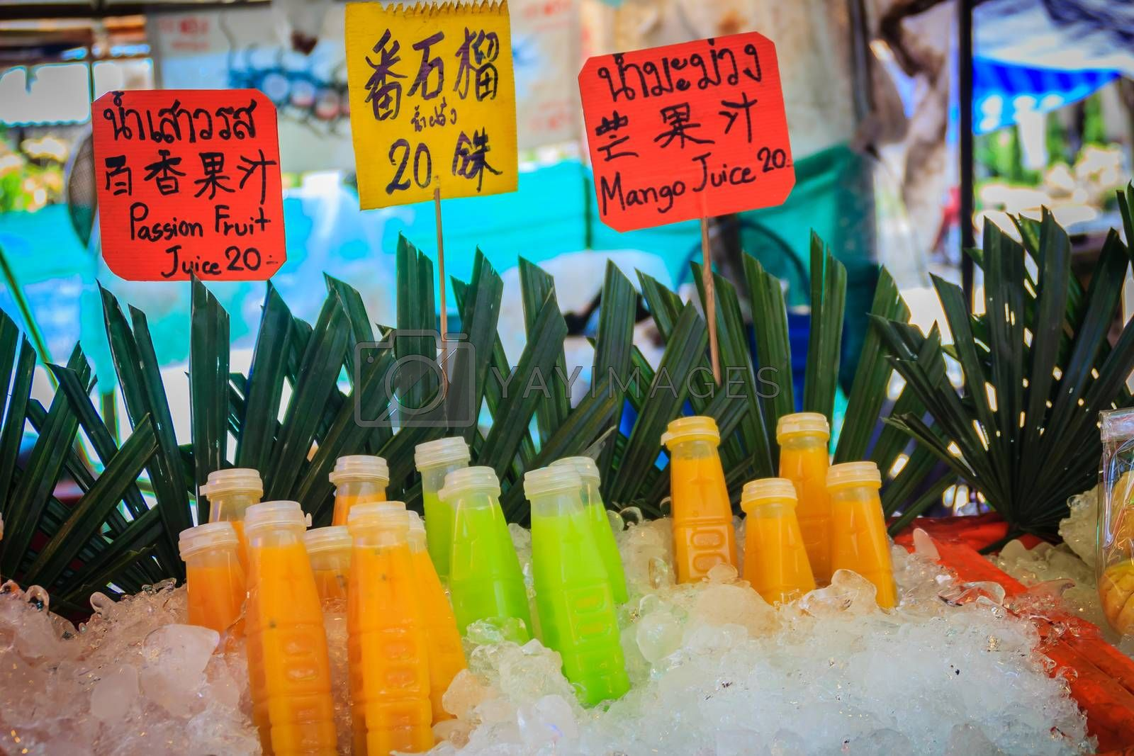 Bottled of passion fruit, guava, and mango juices on ice box were displayed for sale as fresh fruits juice at street food stall with price tag.