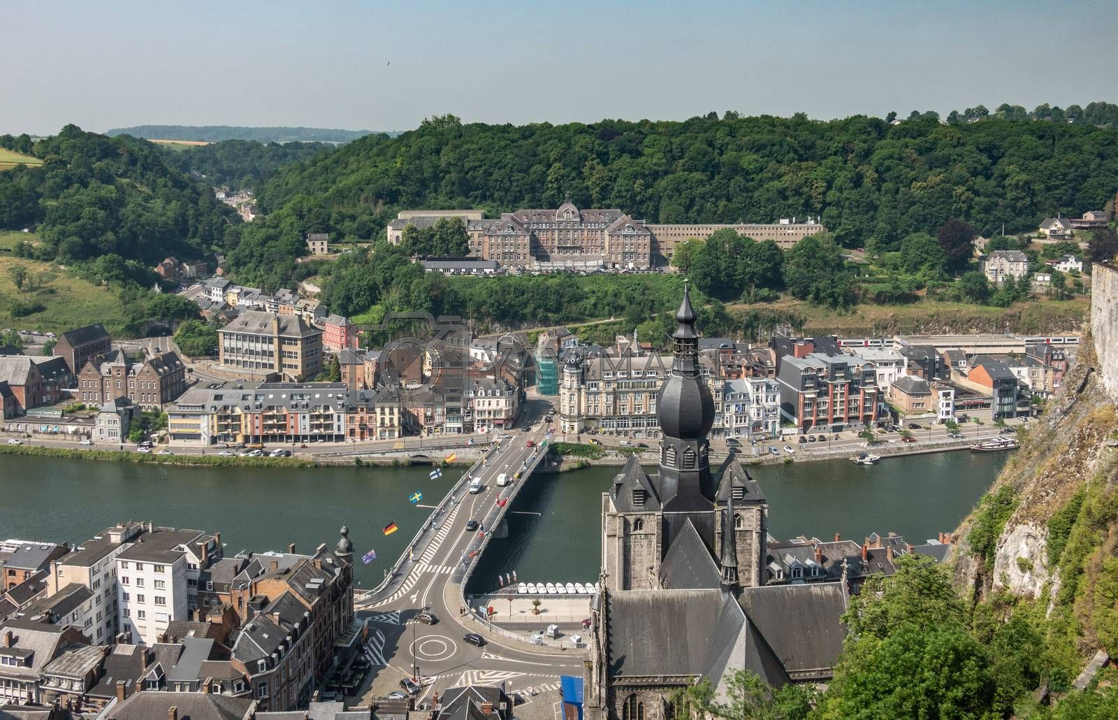 Dinant, Belgium - June 26, 2019: Seen from Citadelle. Large building on top is College Notre Dame de Bellevue, school system from primary to high school. Forests in back. City, river and church