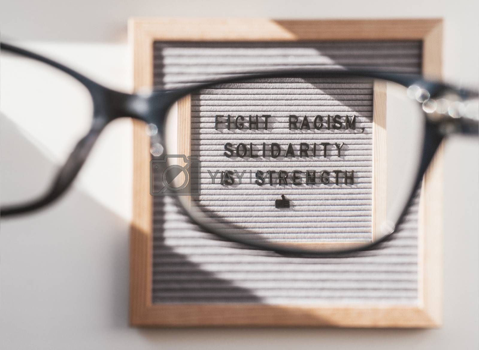 Top view on letter board with words Fight Racism, Solidarity is Strength through eyeglasses. Flat lay concept with actual statement. Social issue. Closer look on race problem in society.