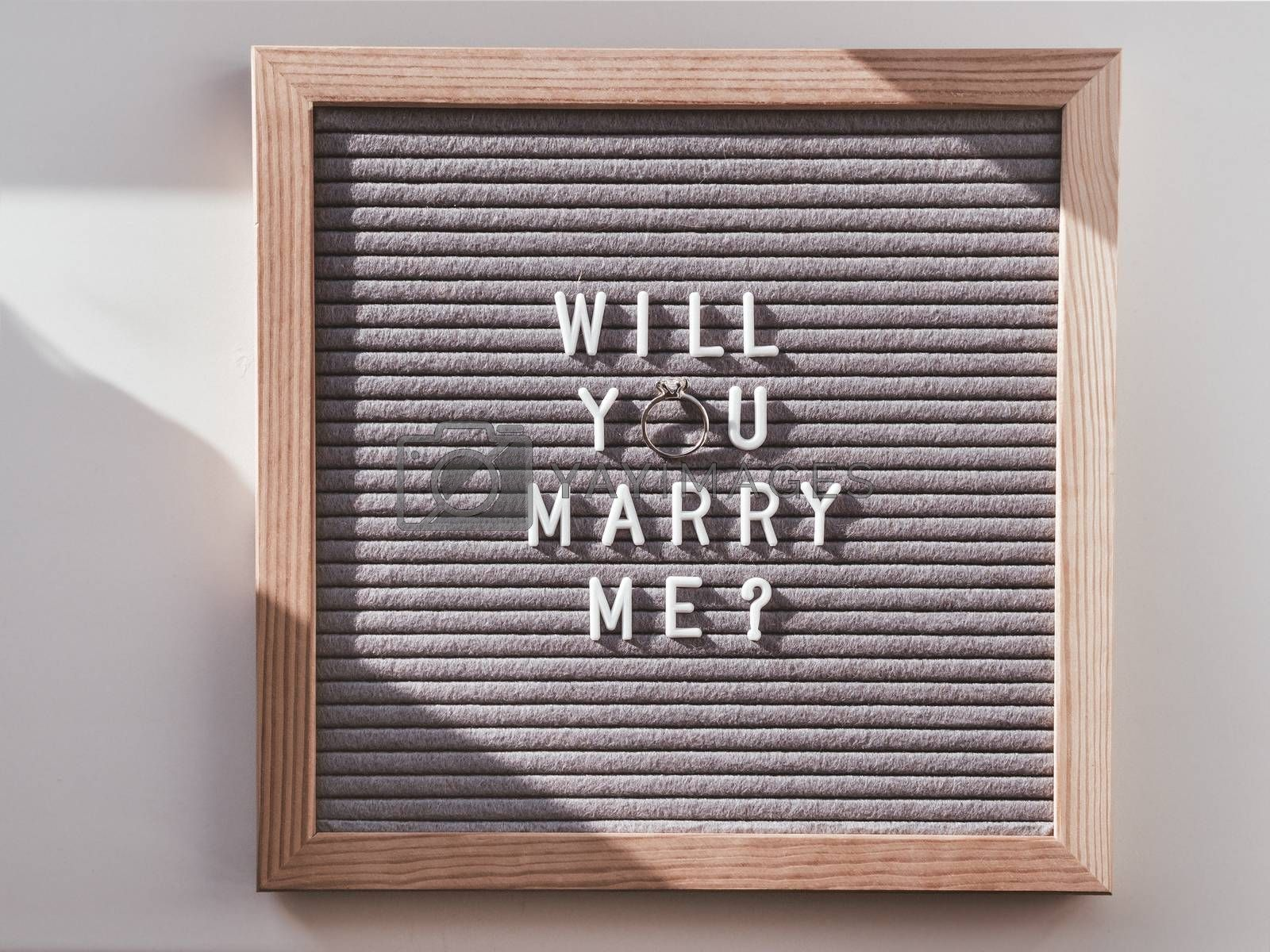 Top view on letter board with wedding proposal - Will You Marry Me? Flat lay concept of creative way to impress future bride. Engagement ring with diamond.