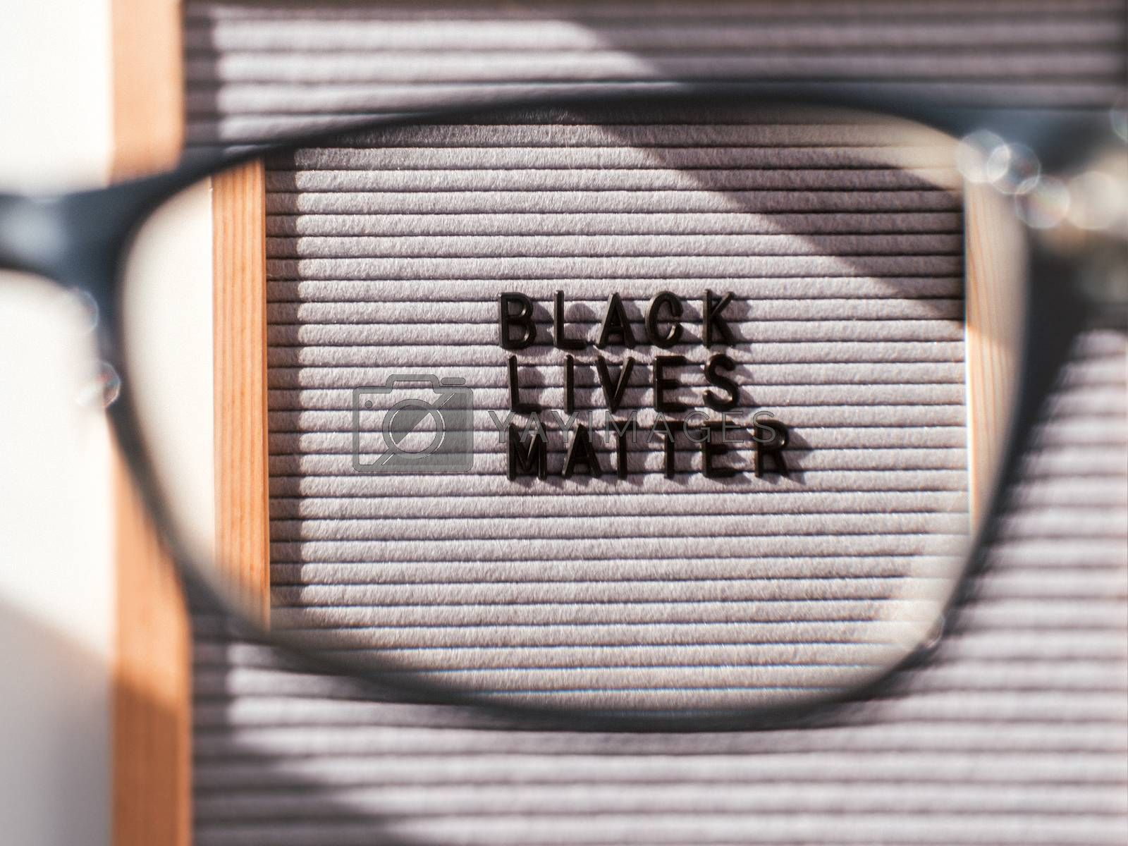 Top view on letterboard with words Black Lives Matter through eyeglasses. Flat lay concept with actual statement. Social issue. Closer look on race problem in society.