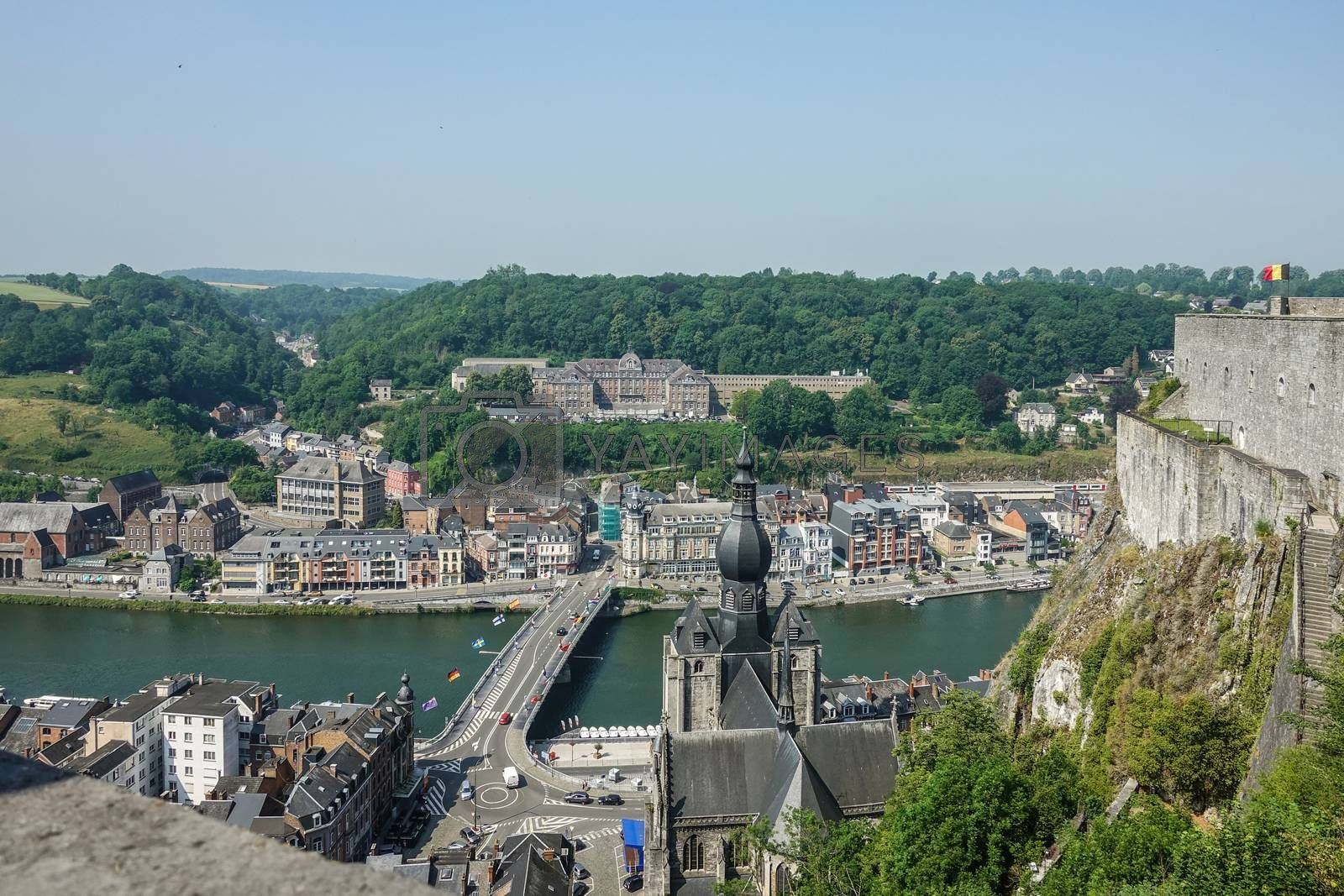Dinant, Belgium - June 26, 2019: Seen from Citadelle. Large building on top is College Notre Dame de Bellevue, school system from primary to high school. Forests in back. Church and ramparts of Citadelle.