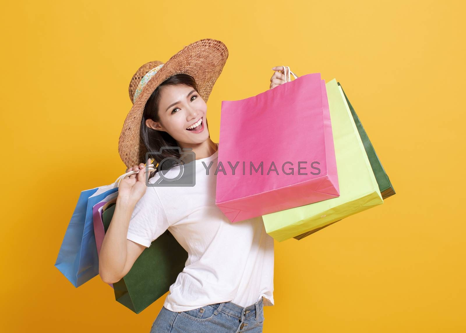 young woman in summer hat and holding shopping bags