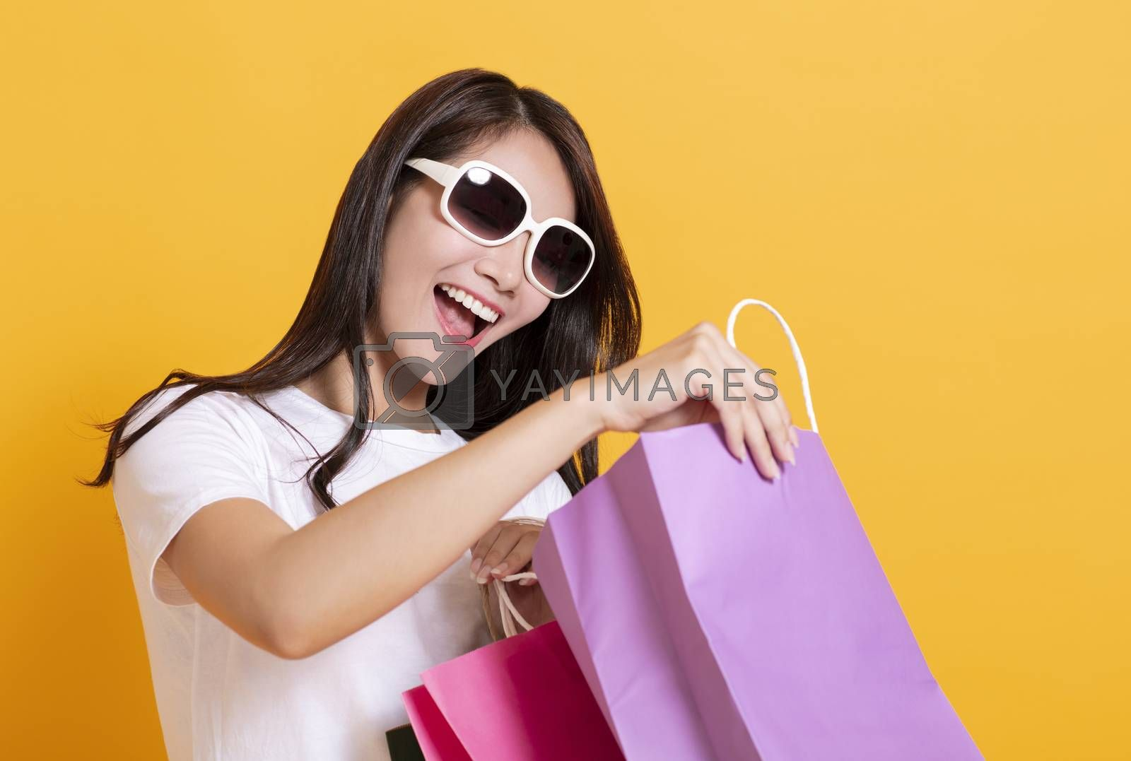 surprised young woman in sunglasses and watching the shopping bags