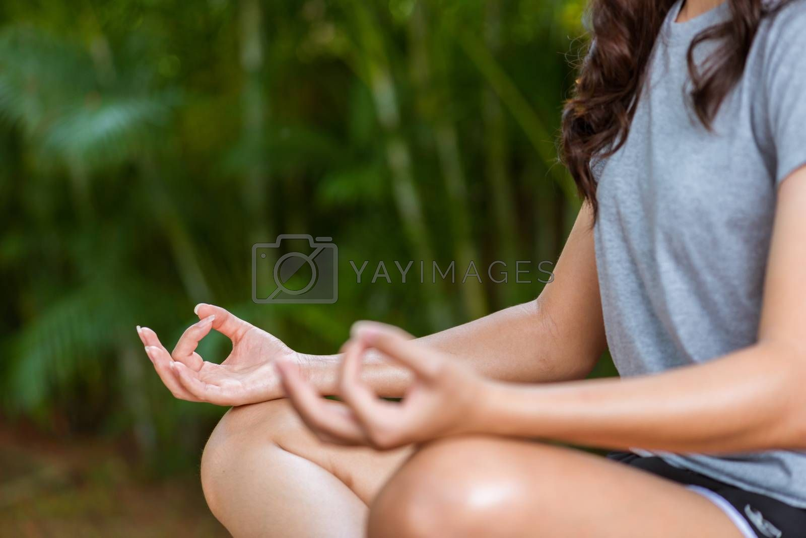 young women practices yoga and meditation in peaceful green gard by Lerttanapunyaporn