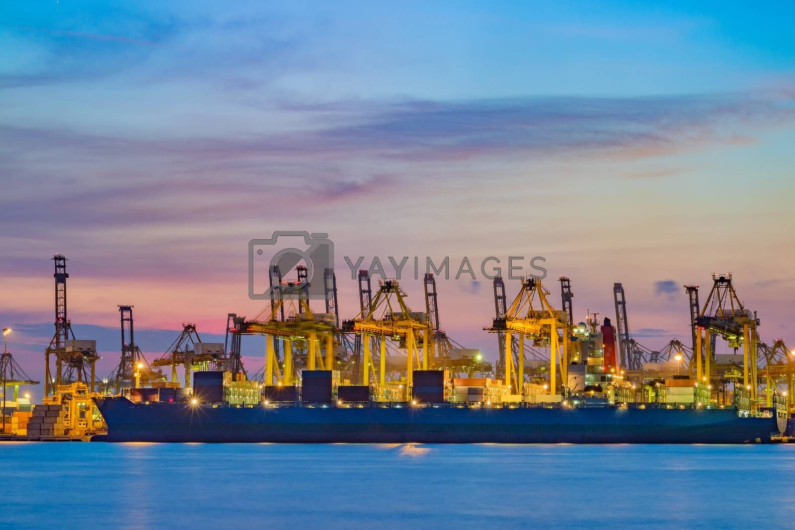 Freighter ship loading cargo at loading dock on twilight time.  by Tanarch