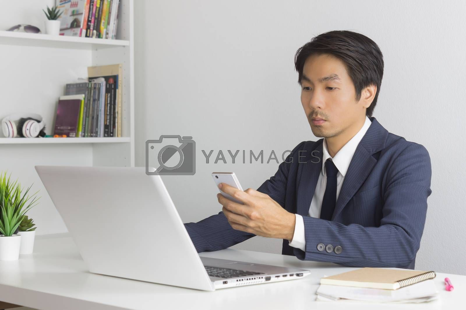 Asian Financial Advisor or Asian Consulting Businessman Contact with Customer by use Smartphone and Laptop in office. Asian Financial Advisor or Asian Consulting Businessman chat and send message with customer