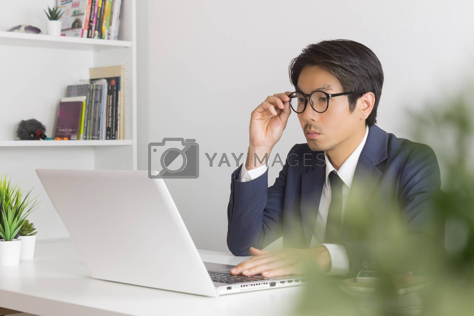 Asian Financial Advisor or Asian Consulting Businessman Seriously Calculate the Financial Data in front of Laptop. Asian financial advisor or Asian consulting businessman working in office
