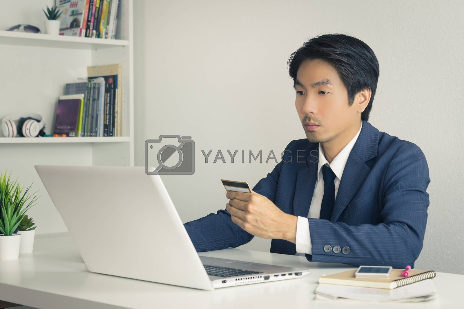 Asian Businessman in Suit Shopping Online by use Credit Card. Asian Businessman enter security code from credit card to shopping online system