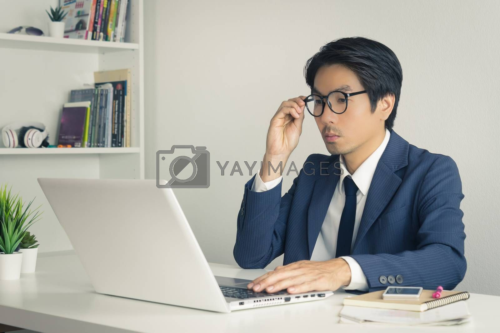 Asian Financial Advisor or Asian Consulting Businessman in Suit Consider and Analyze Financial Data. Asian Financial Advisor or Asian Consulting Businessman serious working in office