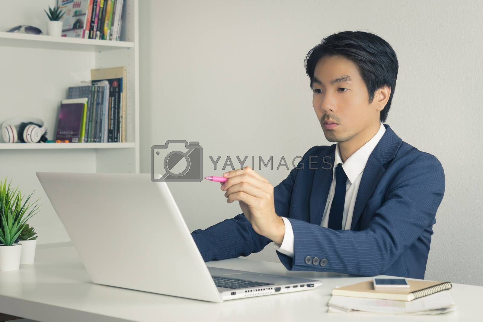 Asian Financial Advisor or Asian Consulting Businessman in Suit Suggest Customer Via Internet. Asian Financial Advisor or Asian Consulting Businessman working in office
