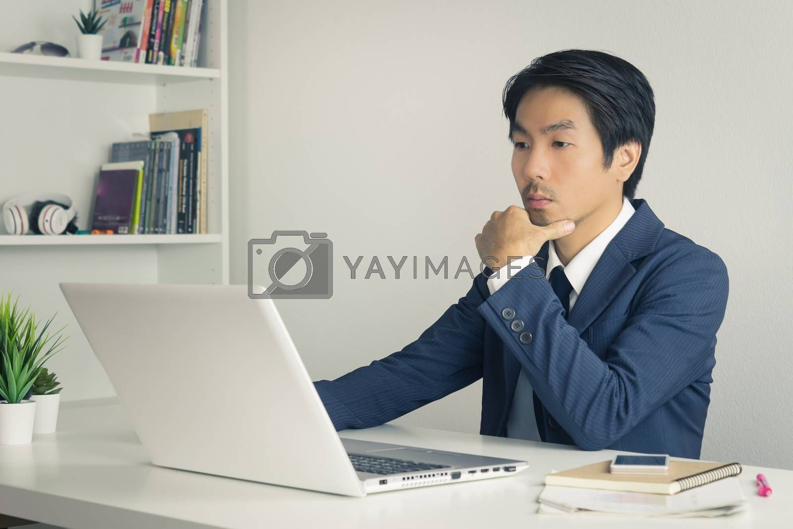 Asian Financial Advisor or Asian Consulting Businessman in Suit Thinking in front of Laptop Monitor in Office. Asian financial advisor or Asian consulting businessman contact with customer