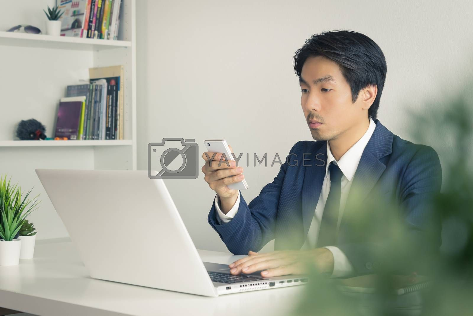 Asian Financial Advisor or Asian Consulting Businessman Use Smartphone and Laptop in Office. Asian financial advisor or Asian consulting businessman contact with customer
