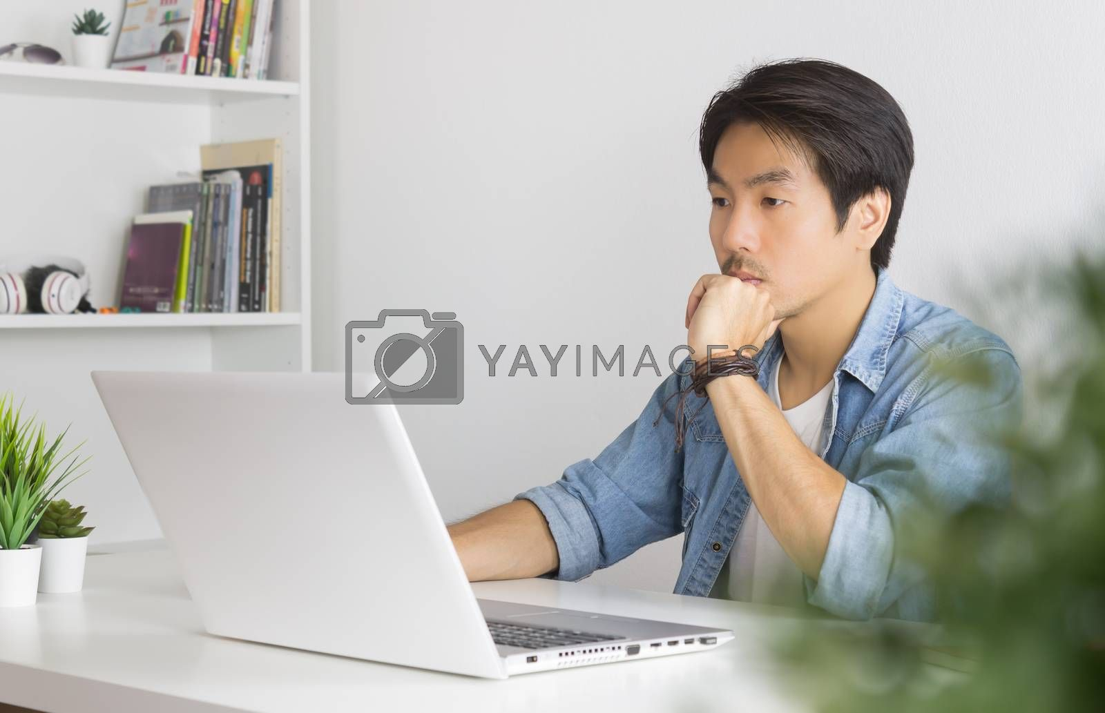 Portrait Asian Casual Businessman in Denim or Jeans Shirt Use Laptop and Thinking and Serious Pose in Home Office. Casual businessman working with technology