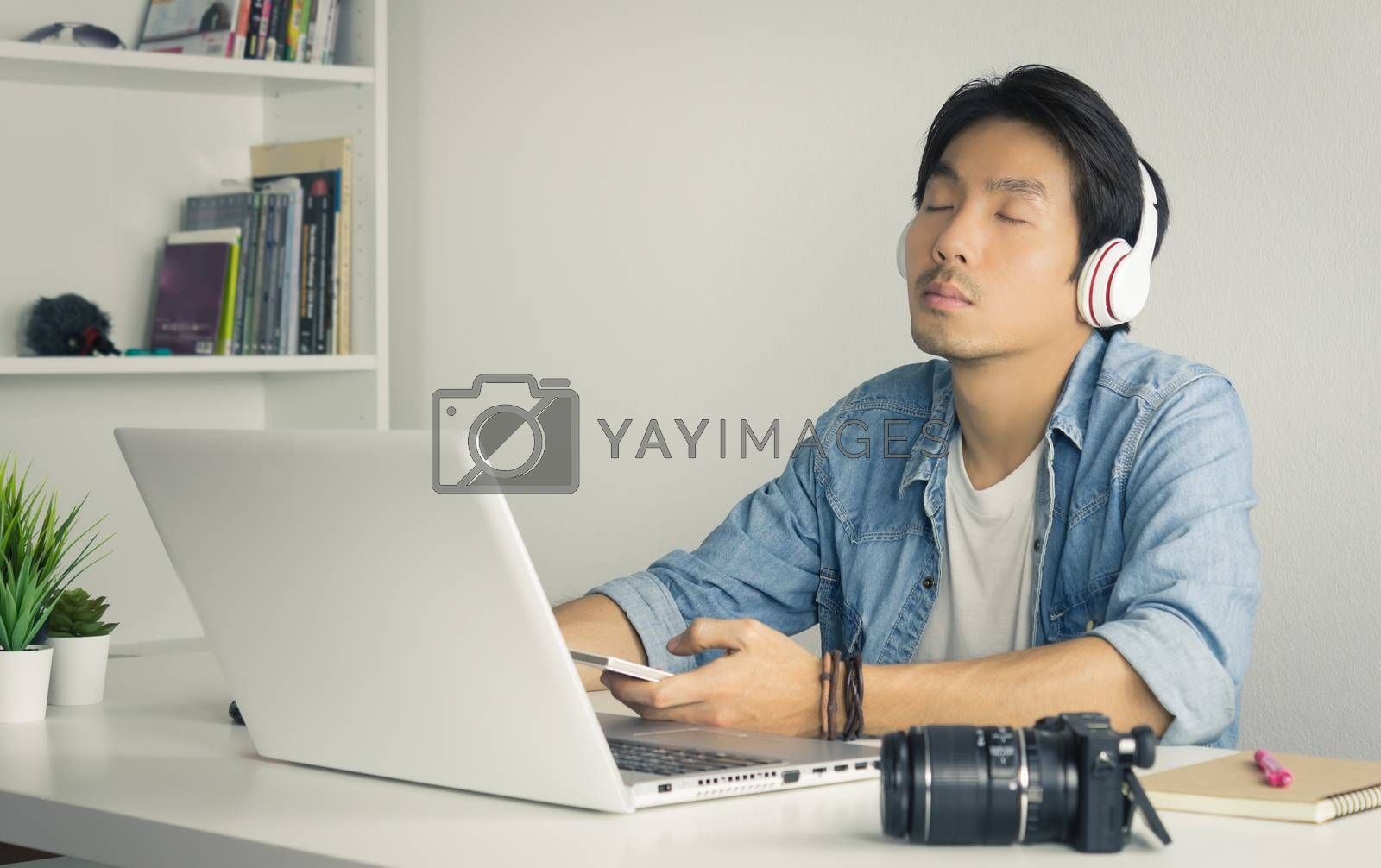 Portrait Asian Photographer with Laptop and Smartphone and Headphone in Home Office. Photographer listening to music by use bluetooth technology in smartphone