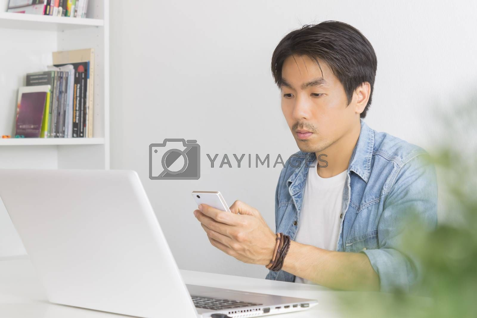 Young Asian Casual Businessman Send Messages to Colleague at Workplace in Home Office. Casual business or informal business in home office