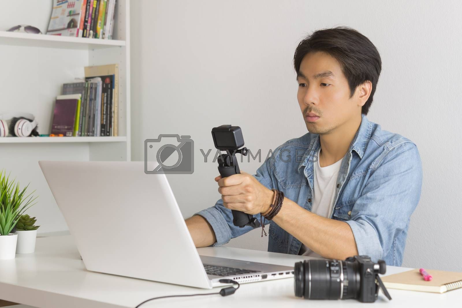 Asian Photographer or Freelancer in Denim or Jeans Shirt Selfie or Take Photo by Action Camera in Front of Laptop in Home Office. Photographer or freelancer working with technology