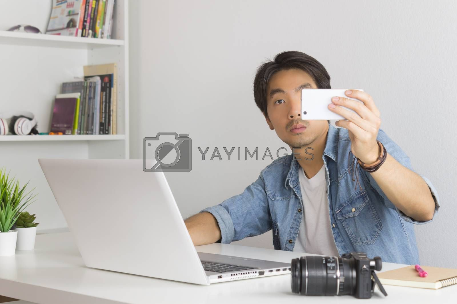 Asian Photographer or Freelancer in Denim or Jeans Shirt Selfie or Take Photo by Smartphone in Front of Laptop in Home Office. Photographer or freelancer working with technology