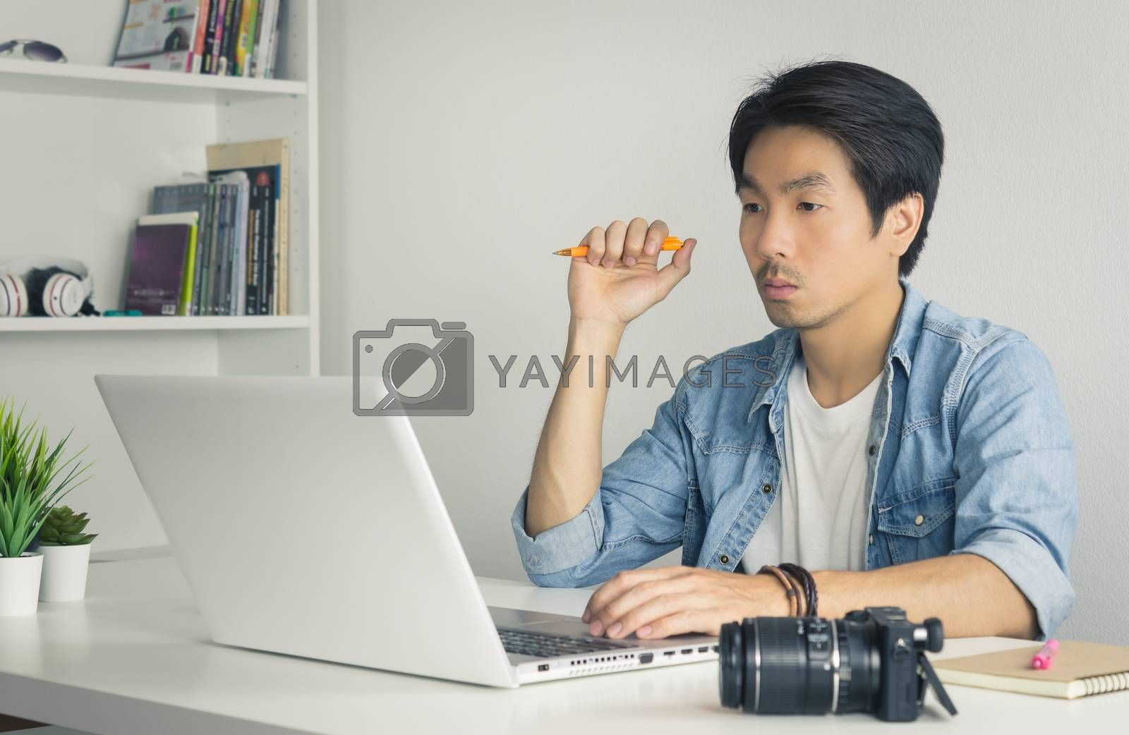 Asian Photographer or Freelancer in Denim or Jeans Shirt Hold Pen and Thinking in Front of Laptop in Home Office. Serious photographer or Freelancer working with technology