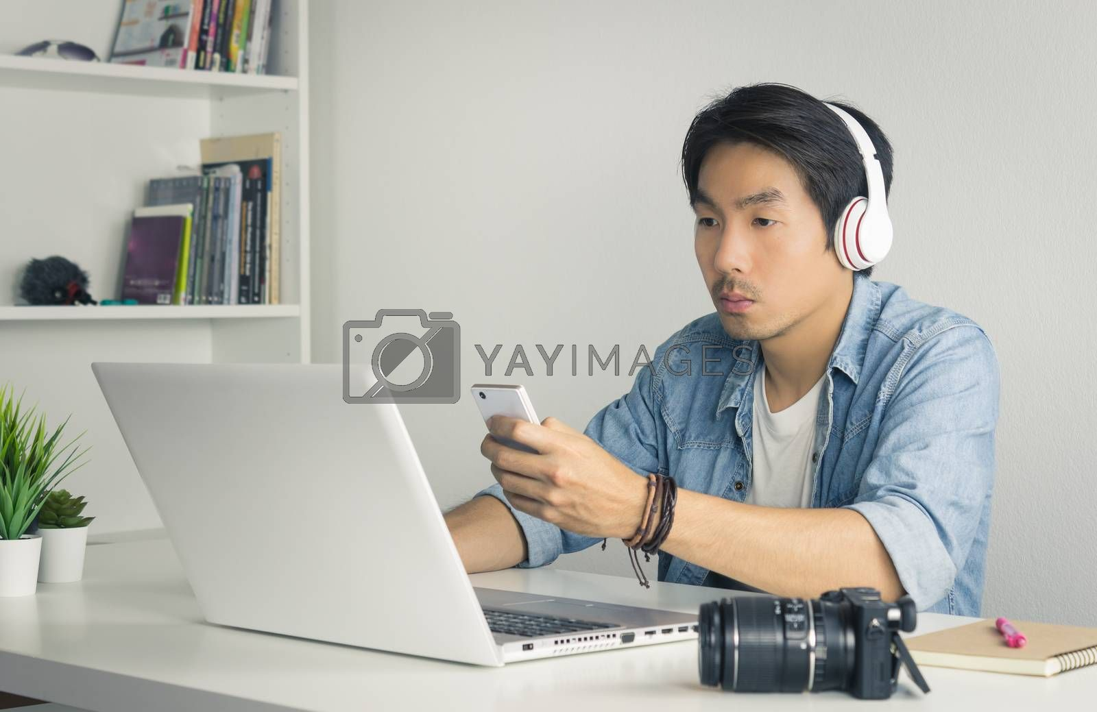 Asian Freelance Videographer in Denim or Jeans Shirt Checking Multimedia File by Smartphone with Laptop in Home Office. Freelance Videographer working with technology