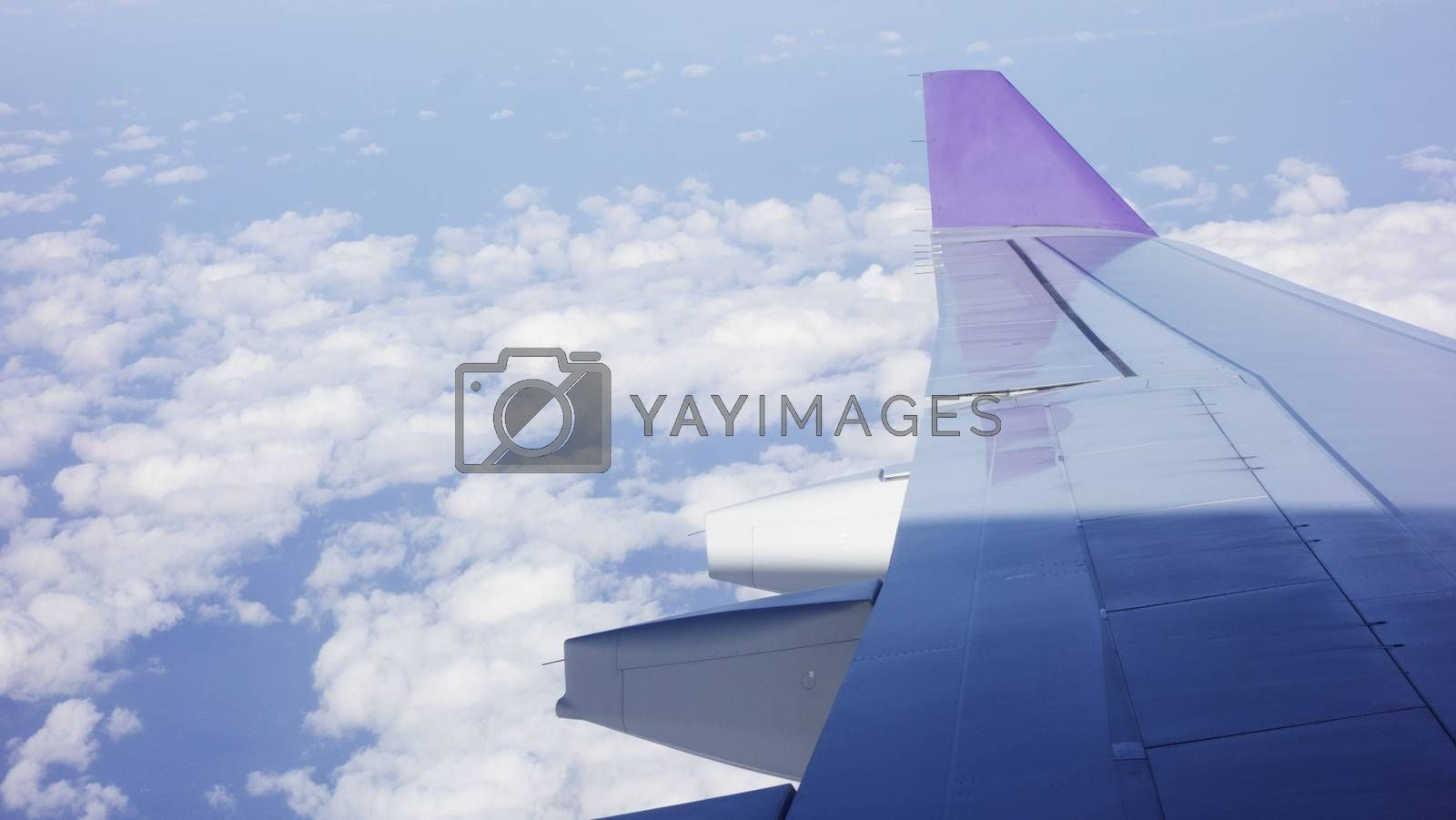 Wing of an airplane flying above the morning clouds by Kingsman911